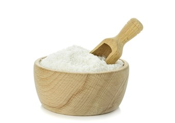 Desiccated coconut in wooden bowl with scoop on white background