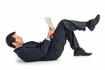 Businessman lying on the floor while reading a book