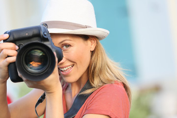 Woman photographer taking picture of model outside