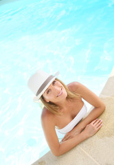 Attractive woman with hat posing by swimming-pool