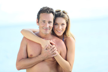 Portrait of middle-aged couple embracing by the beach