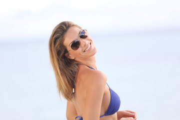 Blond woman in bikini with eyeglasses posing by the beach