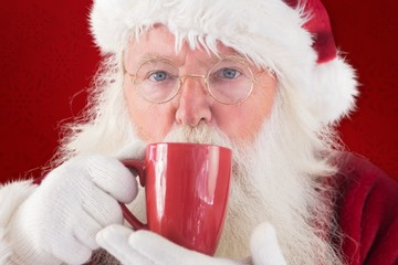 Composite image of santa drinks from a red cup