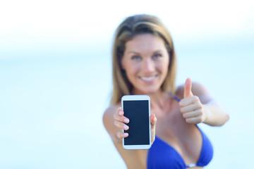 Beautiful woman in bikini showing smartphone to camera