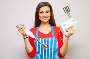 beautiful housewife holding a mixer and a blender in her hands