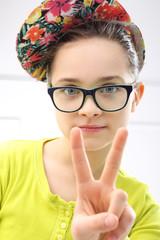 Śliczna dziewczynka pokazuje symbol pokoju