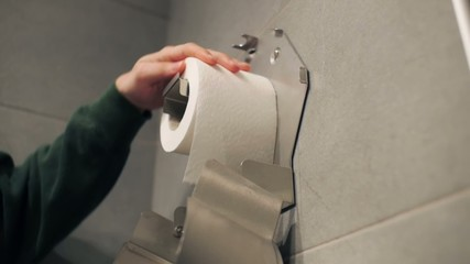 Putting a toilet paper roll into container.