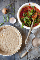 making a wholemeal quiche with red peppers and rocket on mold