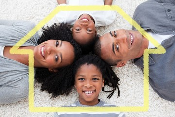 Composite image of smiling young family lying on floor