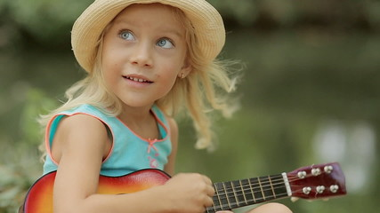 Charming little girl in straw hat playing on toy guitar