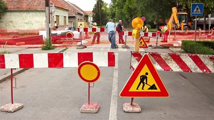 Road signs in a street, under reconstruction symbol
