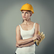 Attractive woman engineer in safety helmet holding gloves