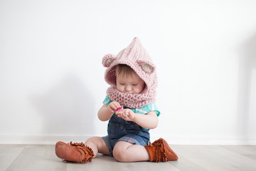Cute baby playing. Snood, jeans, moccs