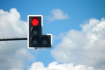 Red light traffic lights against blue sky background.