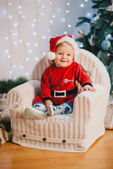 Baby-boy in Santa Claus suit sitting under the Christmas tree