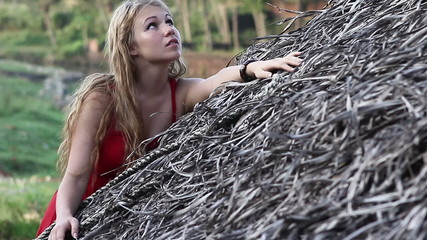young blond woman in red dress stands near a thatched roof