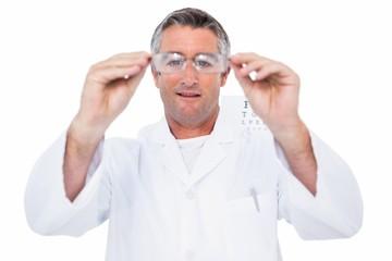 Optician in coat holding glasses
