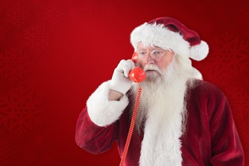 Composite image of santa on his red phone