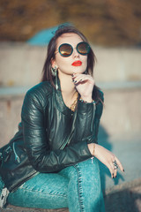 Young fashion beautiful girl in leather jacket and sunglasses