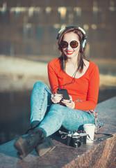Beautiful hipster girl in sunglasses listening music