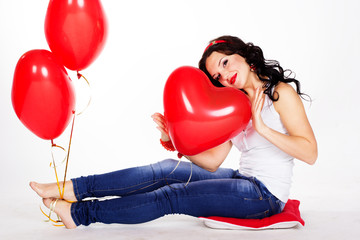Sexy brunette with balloons heart in studio
