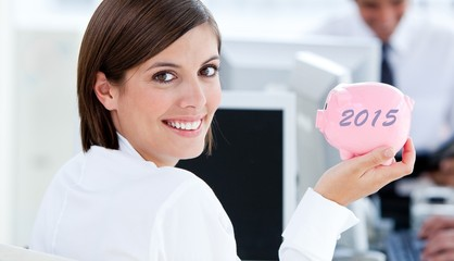 Composite image of happy businesswoman holding a piggybank