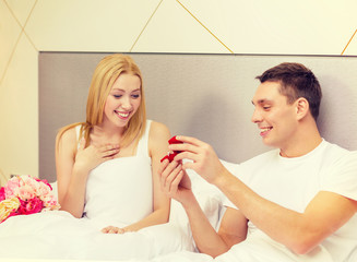 man giving woman little red box and ring in it