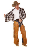 cowboy in chaps holding shirt open poster