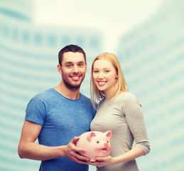 smiling couple holding big piggy bank