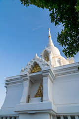 white stupa and buddhist statue in thai temple