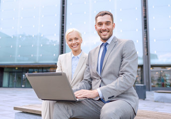 smiling businesspeople with laptop outdoors