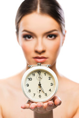 Beautiful woman with clock close up, serious
