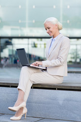 smiling businesswoman working with laptop outdoors