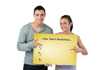Smiling young couple pointing at sign they are holding