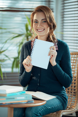 Girl showing blank notebook