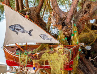 Tree, decorated with old red fishing boat.