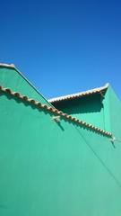 Casa verde con cielo azul