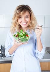 Lachende Frau mit blonden Locken in der Küche liebt Salat