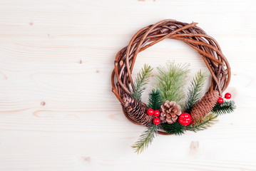 Christmas wreath of twigs with pine needles and cones on light b