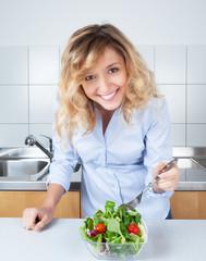 Frau mit blonden Locken in der Küche mag Salat