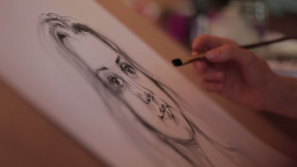 artist paints a portrait of a beautiful woman