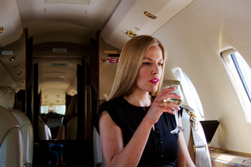 Elegant passenger on plane drinking wine