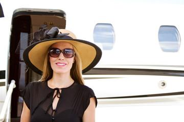Elegant lady standing by jet plane