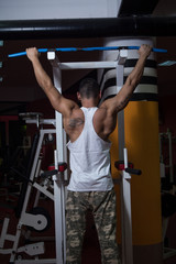 Muscular Young Man Exercising In Gym