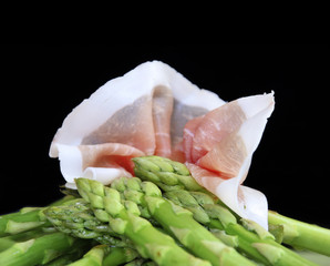 Asparagus with bacon on black background
