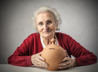 A grandma holding a piggy bank