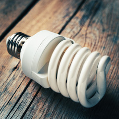 Close up of energy saving light bulb on wooden desk. Vintage sty
