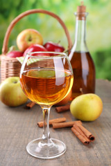 Apple cider in wine glass and bottle, with cinnamon sticks and