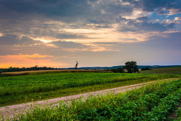 Sunset sky over dirt road and farm fields in rural York County,