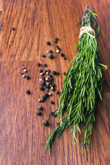 rosemary branch and pepper on brown wooden table